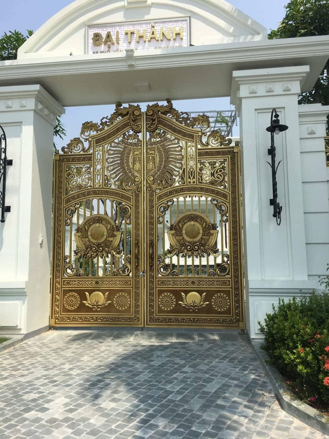 Mẫu cổng nhôm đúc 2 cánh có họa tiết logo mặt nổi